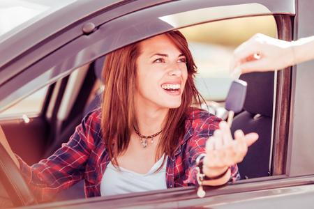 若い陽気な女性の彼女の最初の新しい車にキーを保持しています。顧客満足度。