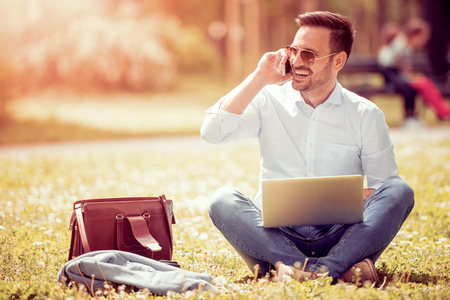 Handsome young man using laptop in park on a summer day.