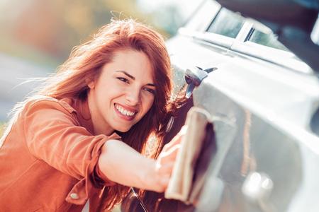 Junge Frau, die ihr Auto draußen säubert. Selbstbedienung, Sorgfaltkonzept.