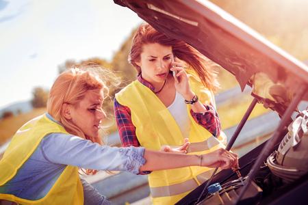 Две женщины со сломанной машиной, ждут помощи Фото со стока