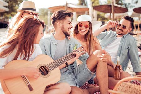Groep vrienden met gitaar met plezier op het strand. Zomer, vakantie, vakantie, muziek, mensenconcept. Stockfoto