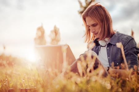 Jonge man in een park genieten van laptop.
