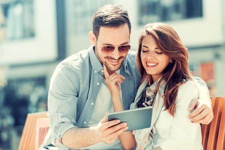 Feliz pareja joven abrazos y riendo al aire libre, tomando selfie.