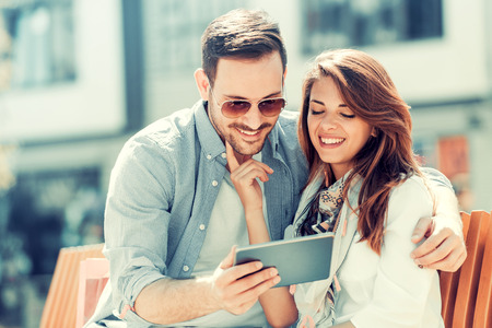 Happy young couple hugging and laughing outdoors,taking selfie.