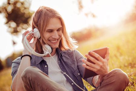 Knappe jonge man genieten van muziek op een zomerdag in het park. Stockfoto