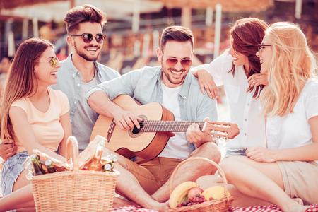 Groep gelukkige jonge mensen die een picknick op het strand hebben, plezier samen hebben. Stockfoto