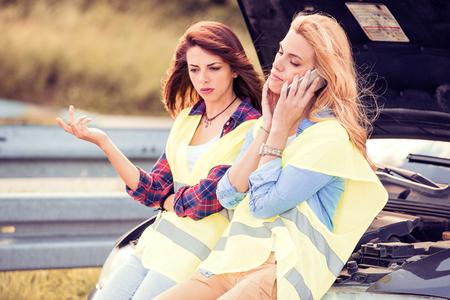 Zwei Frau mit einem kaputten Auto, warten auf Hilfe