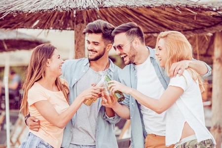 Amigos bebiendo cervezas y escuchando música. Divirtiéndose en la fiesta en la playa. Foto de archivo