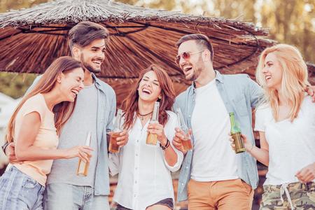 Vrienden drinken bieren en luisteren naar muziek. Veel plezier op strandfeest. Stockfoto