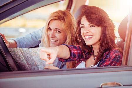 Shot van een twee vrouw met behulp van een kaart tijdens het zitten in de auto.