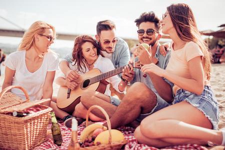 Gruppe von Freunden mit Gitarre Spaß am Strand.Sommer, Urlaub, Urlaub, Musik, Menschen Konzept.