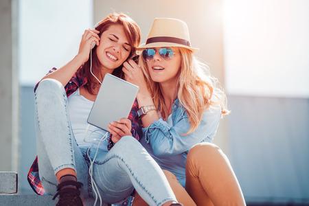 Vrienden luisteren naar muziek op een slimme telefoon in de stad. Stockfoto