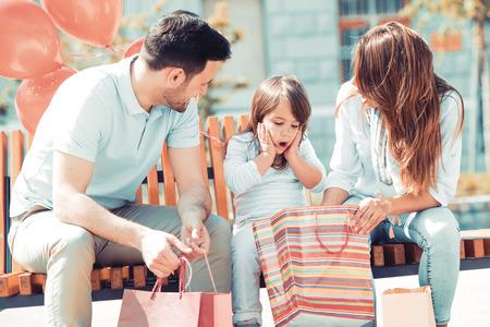 Gelukkige familie met kleine dochter en boodschappentassen in de city.Sale, consumentisme en mensenconcept