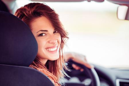 Mooie gelukkige vrouw zit in haar nieuwe auto.