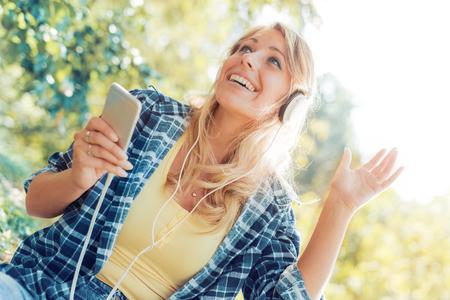 Hübsche junge Frau, die Musik an einem Sommertag im Park genießt.