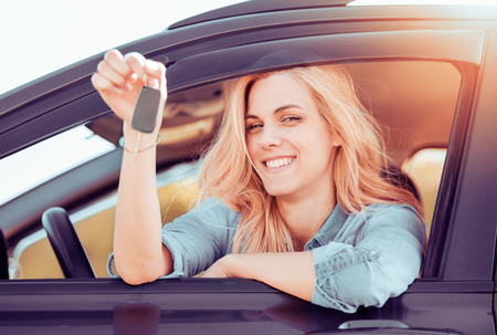 Young cheerful woman holding up keys to her first new car. Customer satisfaction.
