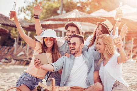 Freunde trinken Biere und hören Musik. Spaß am Strand Party.