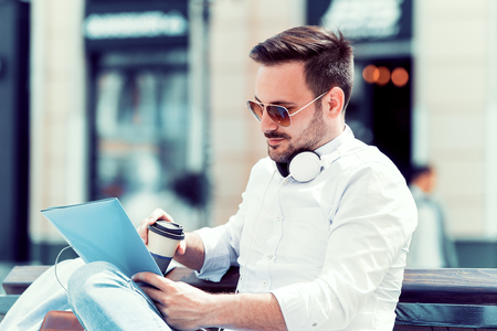 Young businessman drinking coffee to go outside.