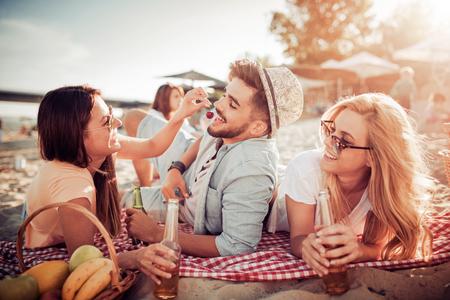 Groep vrienden genieten van zomervakantie op een strand.