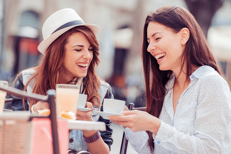 Two beautiful young girls sitting in a cafe, drinking coffee and having a conversation.