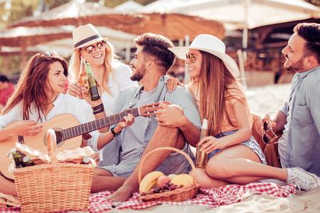 Groep gelukkige jonge mensen die een picknick op het strand hebben. Zomer, vakantie, vakantie, muziek en mensenconcept.