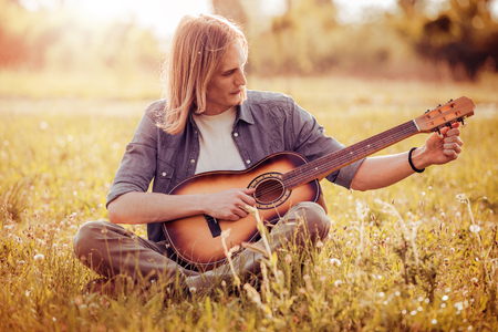 Happy young man playing the guitar while sitting in park.