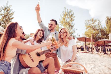 Gruppe glückliche junge Leute, die ein Picknick am Strand haben. Sommer, Feiertage, Ferien, Musik und Leutekonzept.