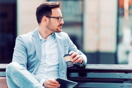 Счастливый улыбающийся бизнесмен, используя цифровой планшет и пить кофе, чтобы выйти на улицу.