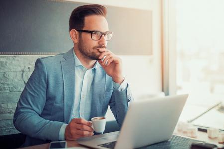 L'homme d'affaires prend une pause dans le café, utilise un ordinateur portable et boit du café.