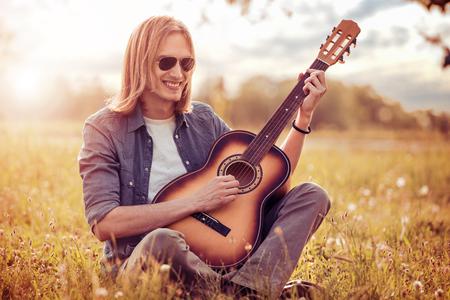 Gelukkige jonge man die gitaar speelt tijdens het zitten in het park. Stockfoto