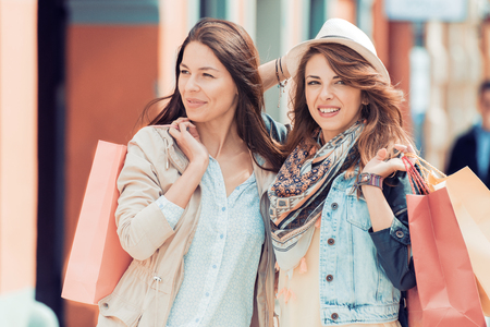Happy young women with shopping bags in the city.Sale,consumerism and people concept. Banque d'images