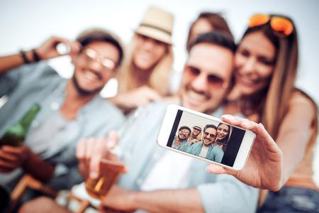 Gelukkige jonge vrienden nemen selfie met slimme telefoon op het strand.