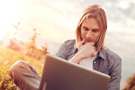 Студент, используя ноутбук на траве в парке.