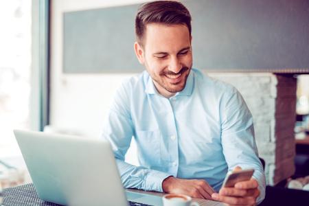 Бизнесмен делает перерыв в кафе, используя ноутбук и пить кофе.
