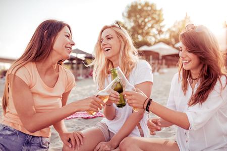 Groep vrouwen met plezier op het strand. Zomer vakantie, vakantie, reis en mensen concept. Stockfoto