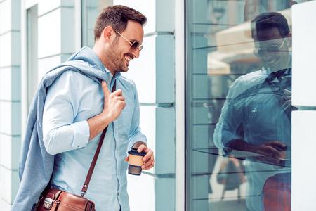 Man die koffie houdt terwijl hij in de stad loopt.
