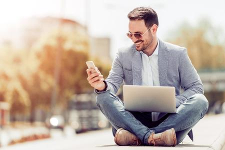 Vrolijke jonge zakenman typen iets op laptop en met behulp van slimme telefoon. Stockfoto