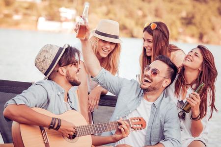 Группа счастливых молодых людей, имеющих пикник на beach.Summer, праздники, отпуск, музыка и люди концепции. Фото со стока