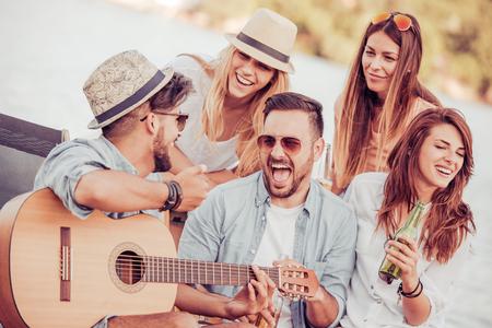 Друзья пили пиво и слушали музыку. Хотелось бы весело провести время на пляже.