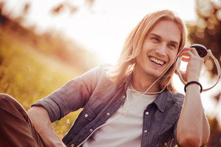 Jonge man zitten op gras en luisteren naar muziek