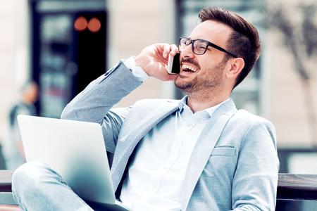 Веселый молодой бизнесмен, набрав что-то на ноутбуке и используя смартфон. Фото со стока