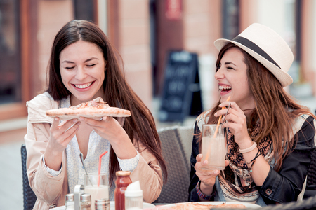 Two cheerful girls eating pizza in a outdoor cafe,relaxing after shopping. Banque d'images - 125697652