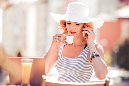 Businesswoman using laptop and sitting at coffee shop.Happy woman working online and using laptop.