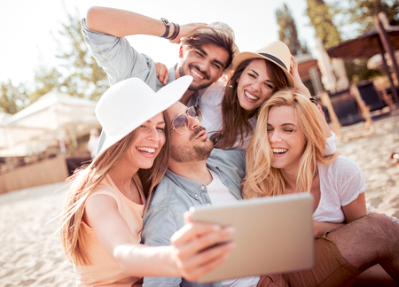 Summer,holidays,vacation and happiness concept-group of friends taking selfie with tablet.