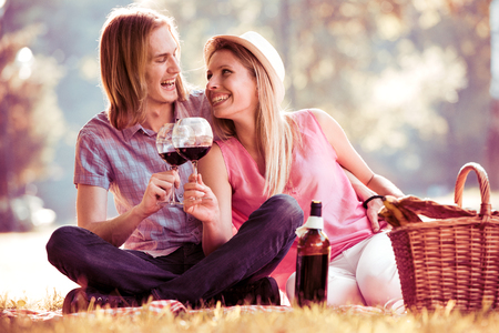Beautiful smiling couple having picnic and tasting red wine.