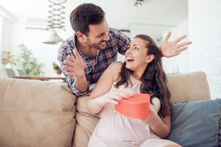 Young woman is happy and surprised with a gift from her husband. Stock Photo
