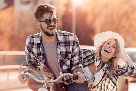 Happy funny young couple riding on bicycle.Love, relationship,romance concept. Stock Photo