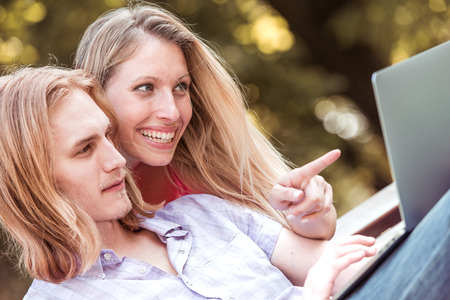 Hermosa pareja feliz con portátil sentado en un banco y viendo la película al aire libre. Foto de archivo