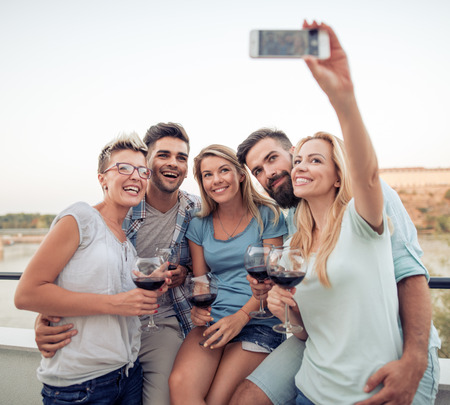 Friends having party outdoors,they are taking selfie.