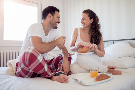 Woman enjoying breakfast in bed with her man. Stock Photo
